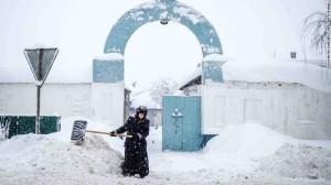 Una suora remove la neve di fronte al cancello del convento Bogoslovsky a circa 190 km da Mosca, 4 Febbraio
